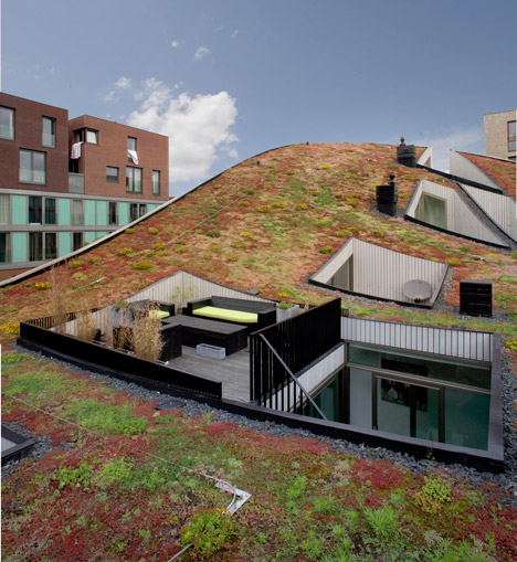 terraces are cut out of the curved green roof of nl