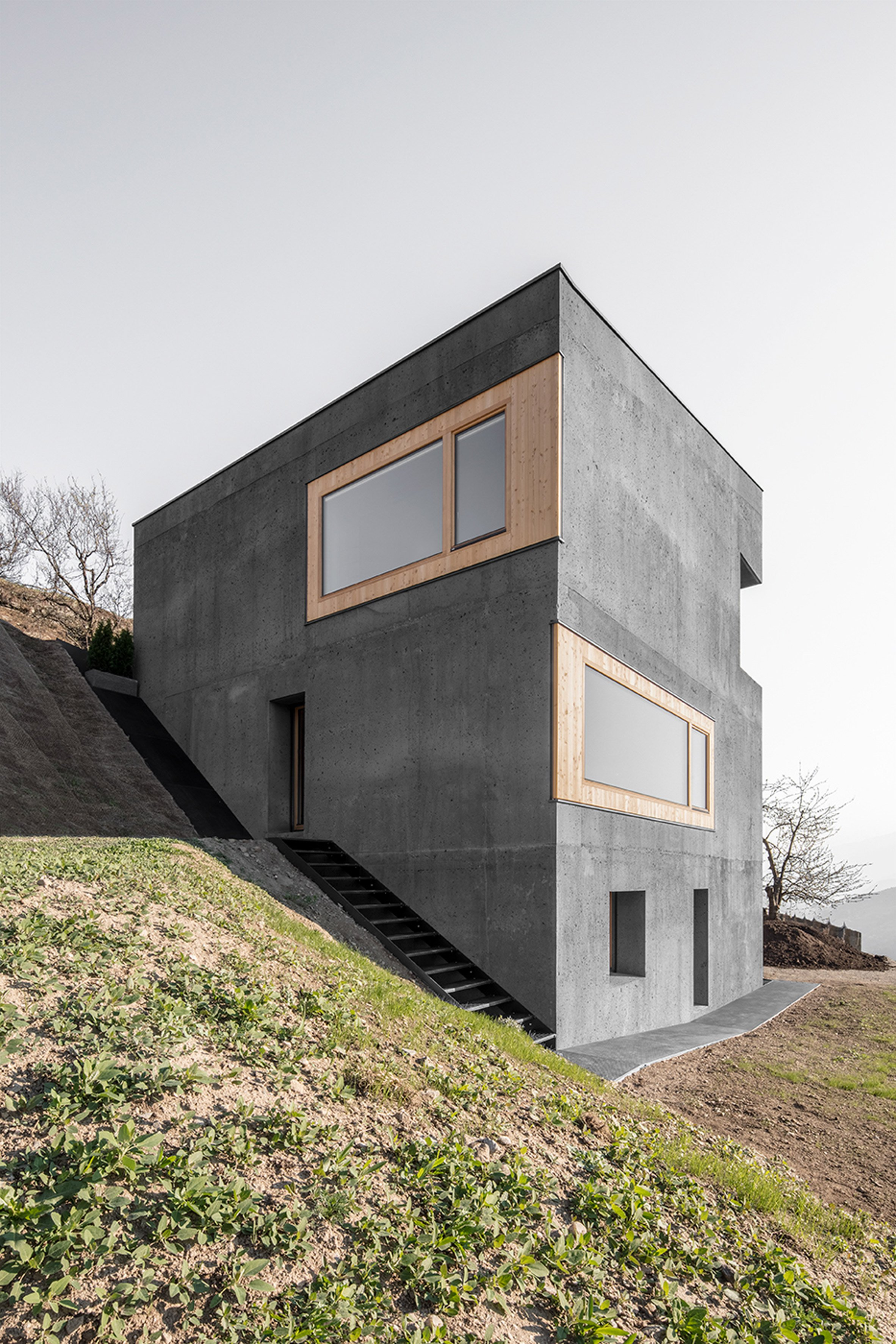 Andreas Gruber embeds minimal concrete house into Tyrolean hillside