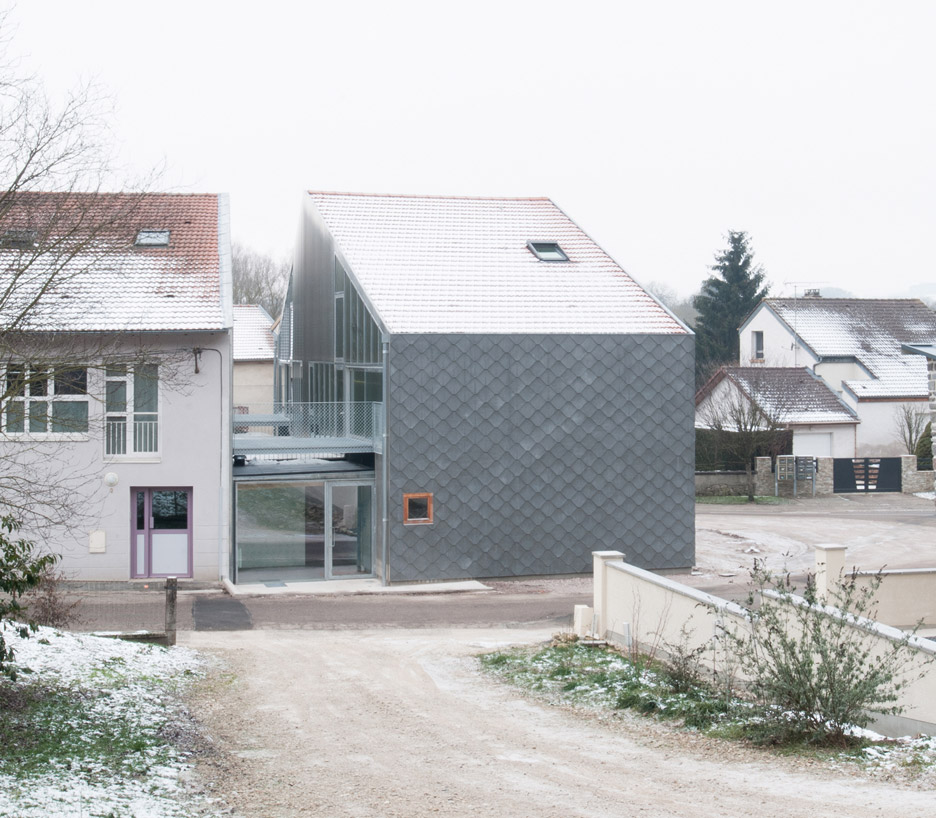 Cement shingles create scaly facade for french barn for Extension architecte
