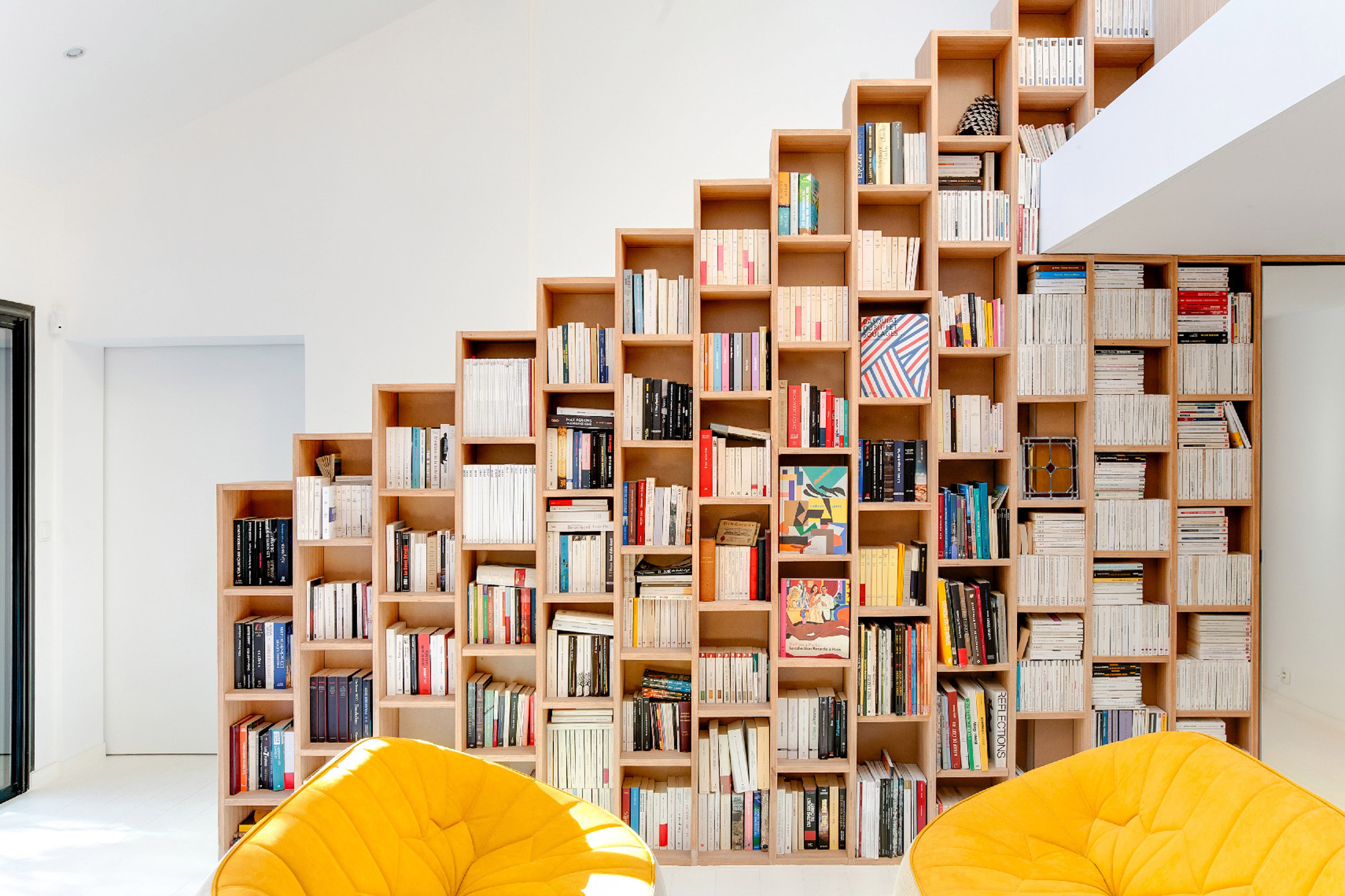 Stepped shelving creates extra storage in Bookshelf House by Andrea Mosca