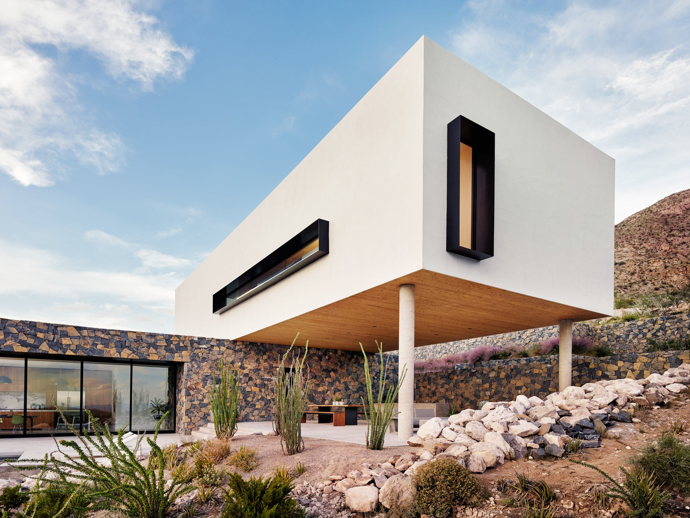 Volcanic stone contrasts with white stucco at Texas desert home by Hazelbaker Rush