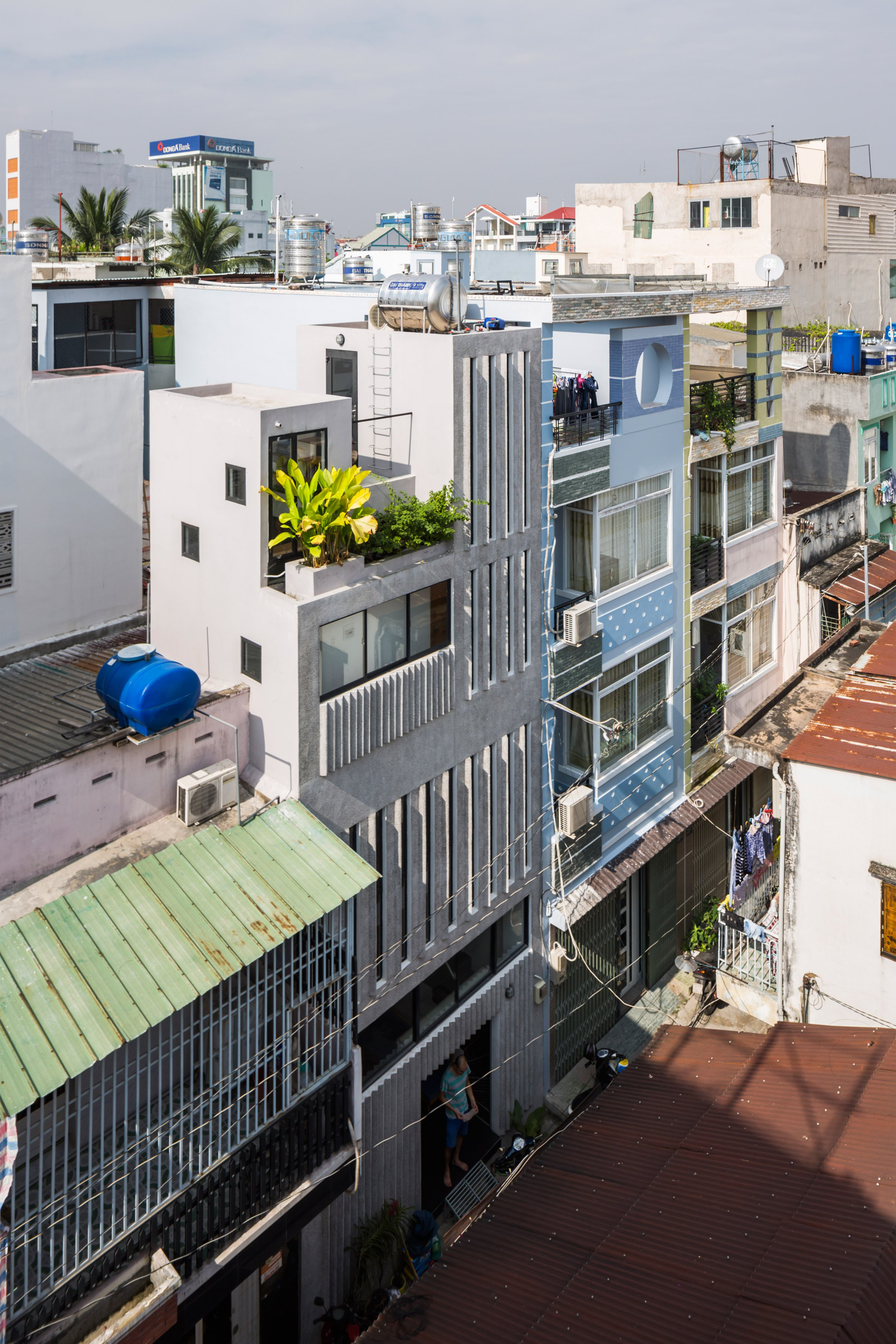 Narrow windows allow daylight into terrazzo-covered house in Ho Chi Minh City