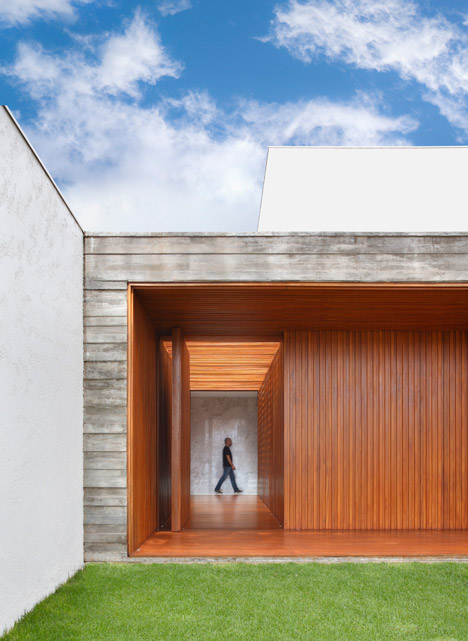 Red wood corridor forms entrance to concrete home in Brazil by Studio Guilherme Torres