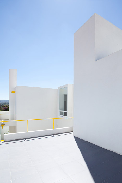 Yellow accents brighten the stacked white volumes of Pino Street House by Oscar Gutiérrez