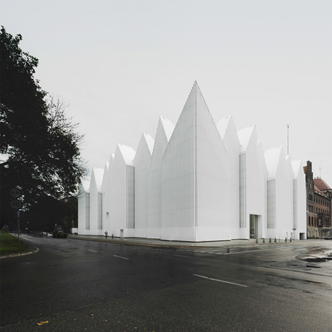 Translucent glass concert hall designed by Barozzi Veiga with a jagged roofline