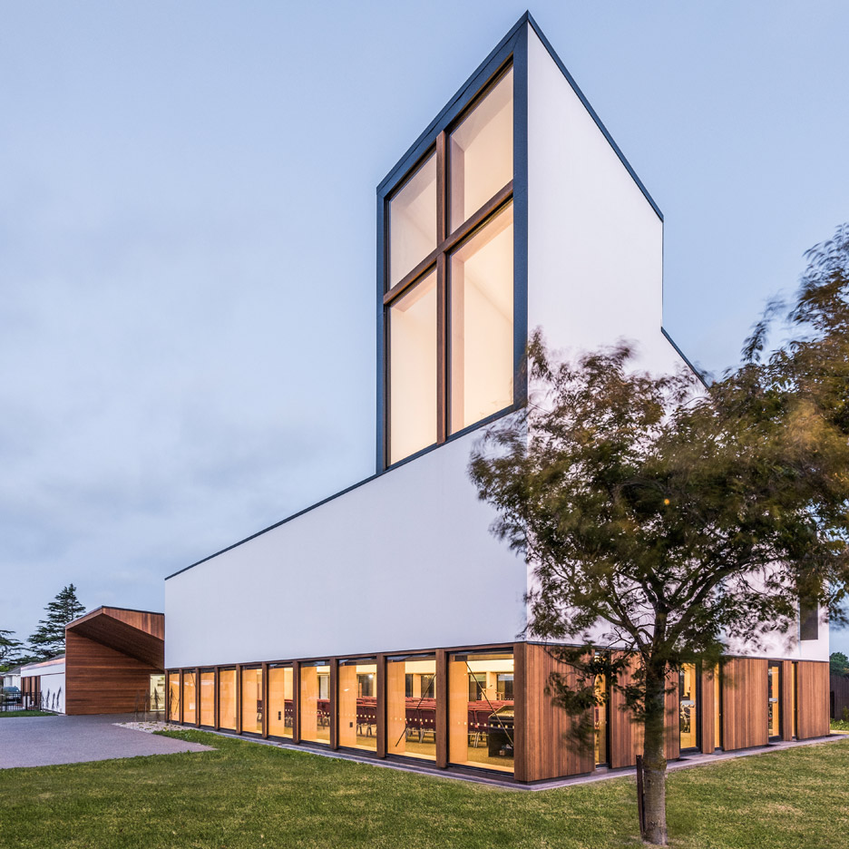 Window with cross-shaped frame forms beacon for rebuilt church by Dalman Architecture