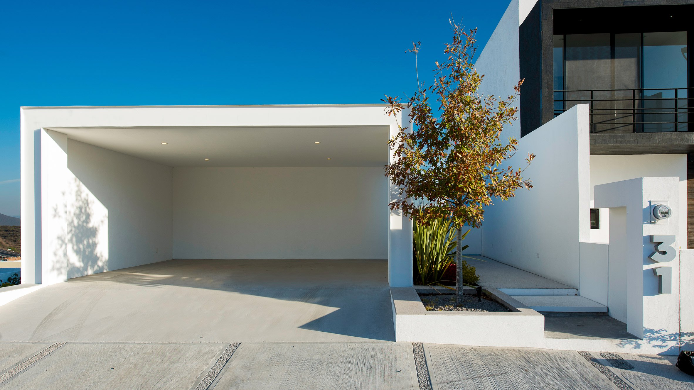Glazing surrounds white house by Evelop Arquitectura to provide vistas of Mexican dale