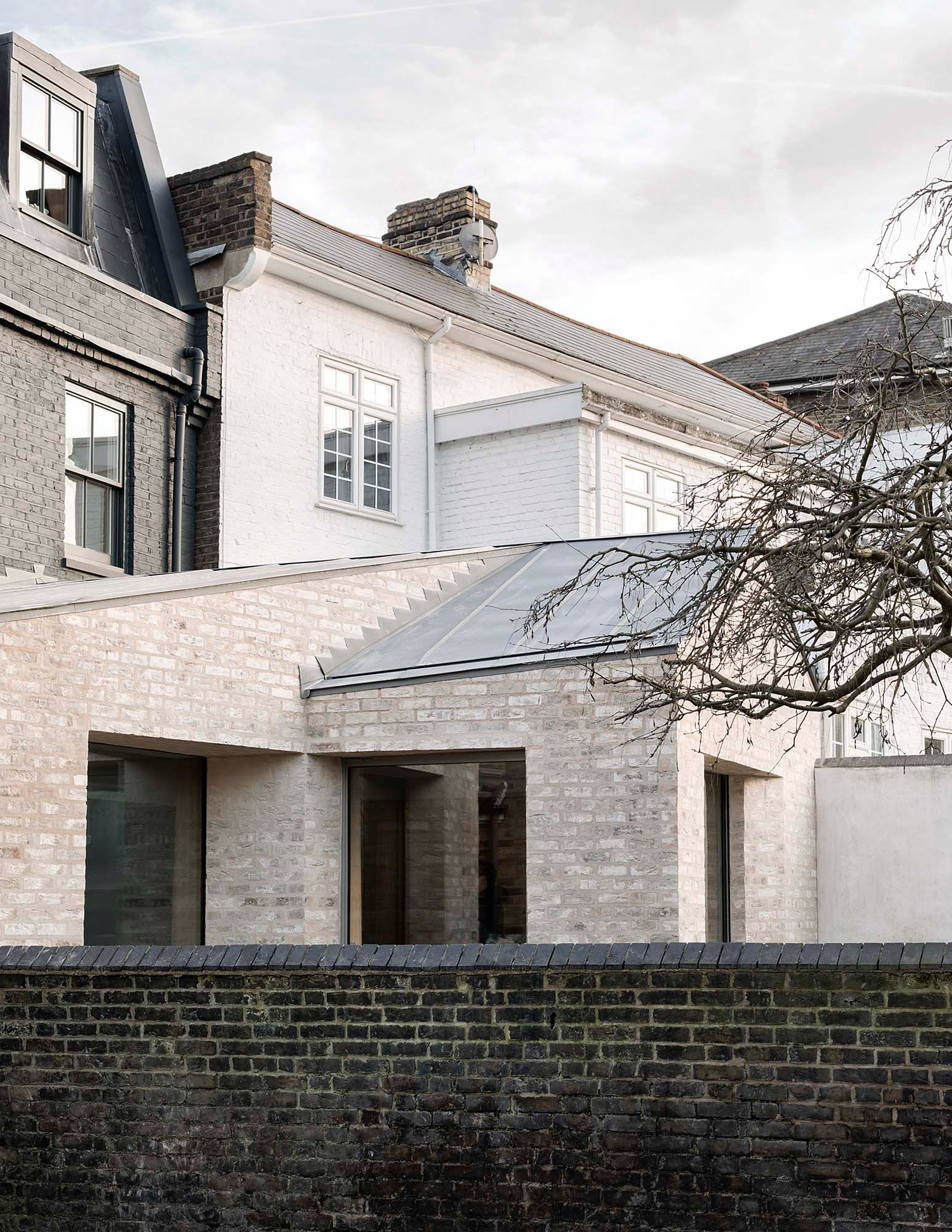 McLaren Excell adds contrasting pale-brick extension to black-painted Victorian house