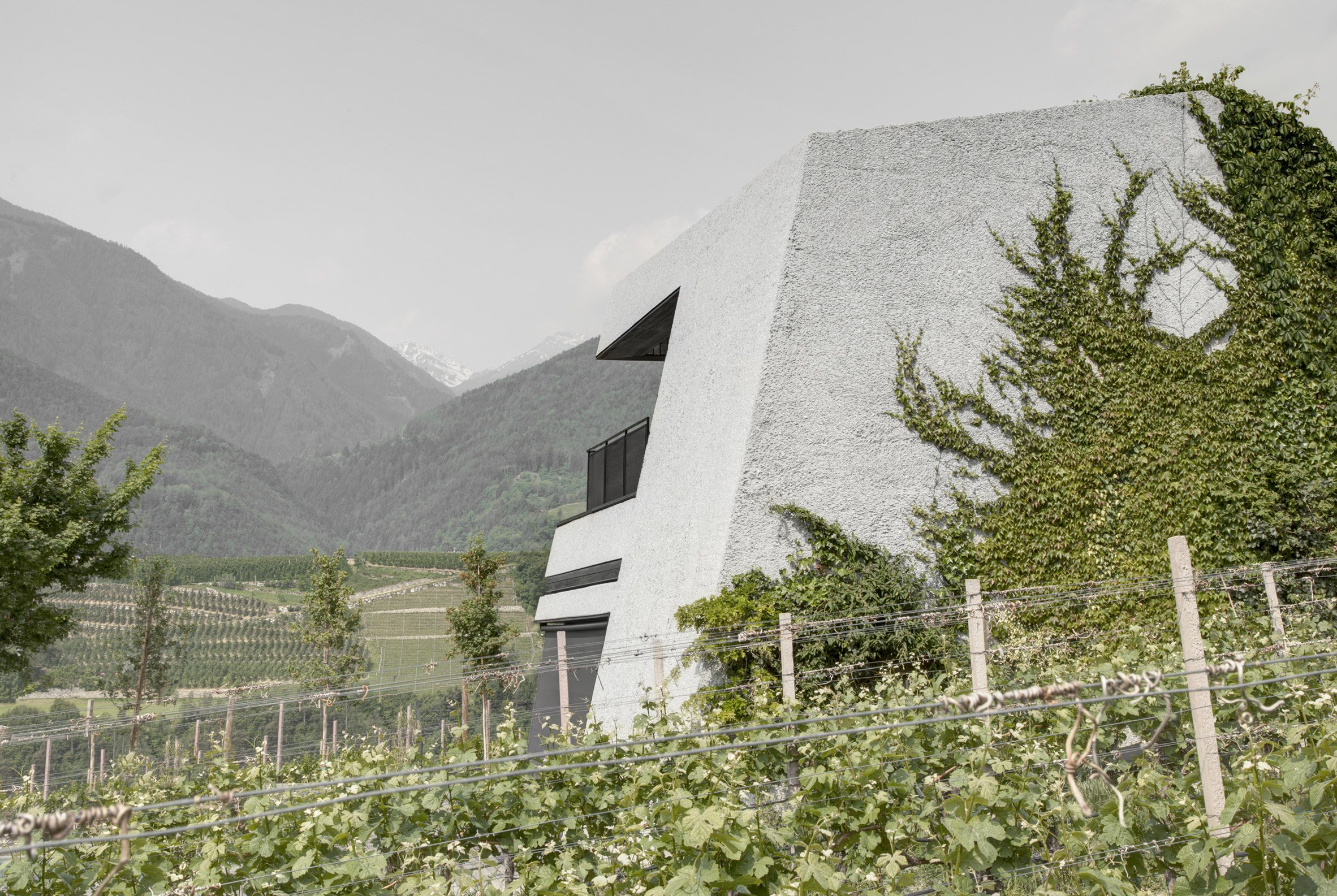 Monolithic concrete house by Bergmeisterwolf emerges from an Alpine hillside