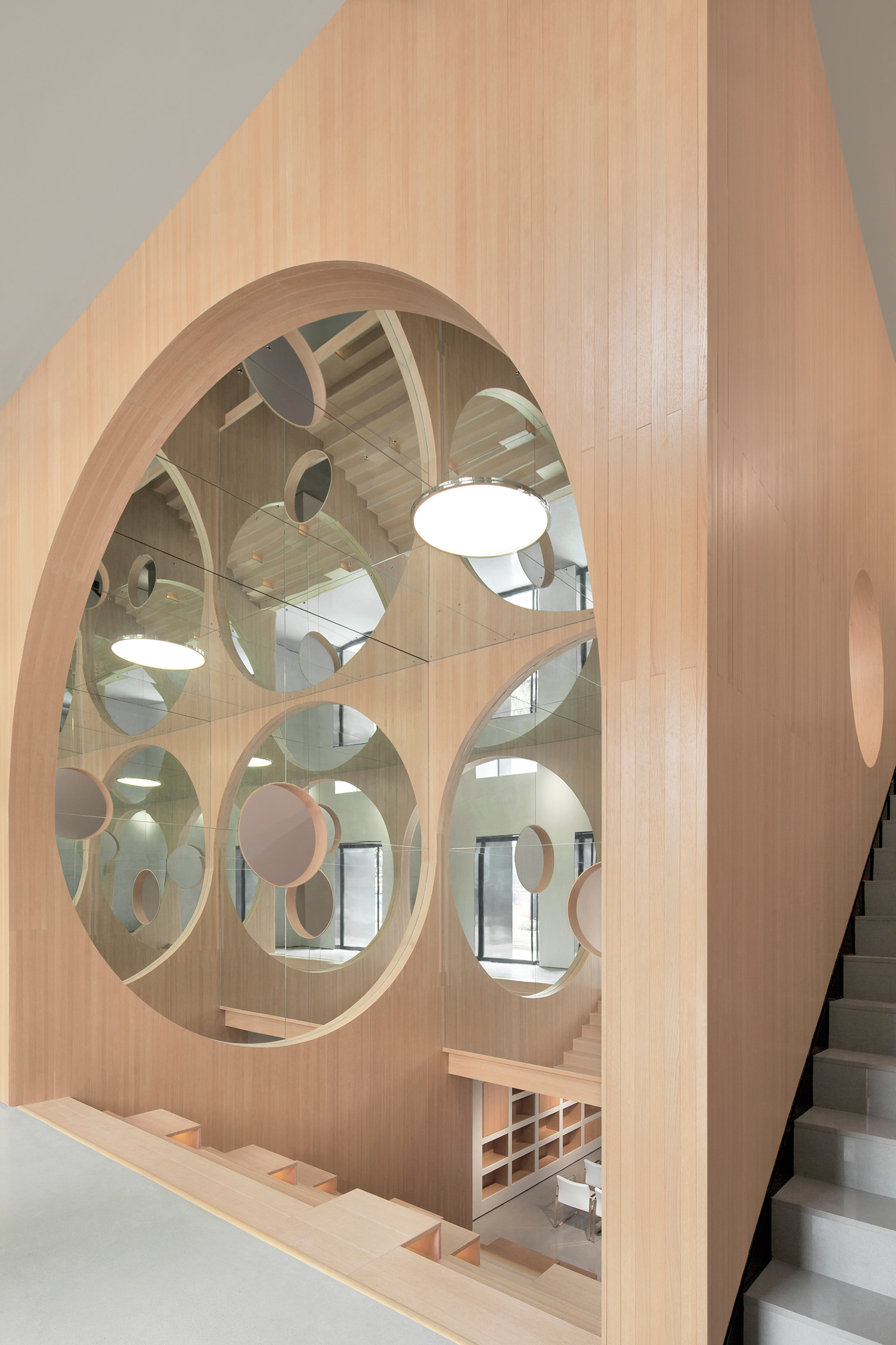 Mirrors reflect arched openings and steps inside wooden auditorium by Penda