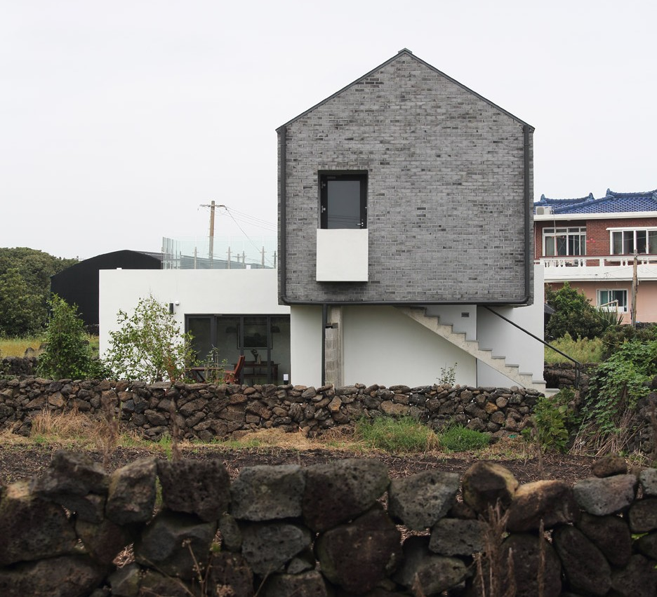 Z Lab uses volcanic stone and pale grey brick for gabled holiday home on Jeju island
