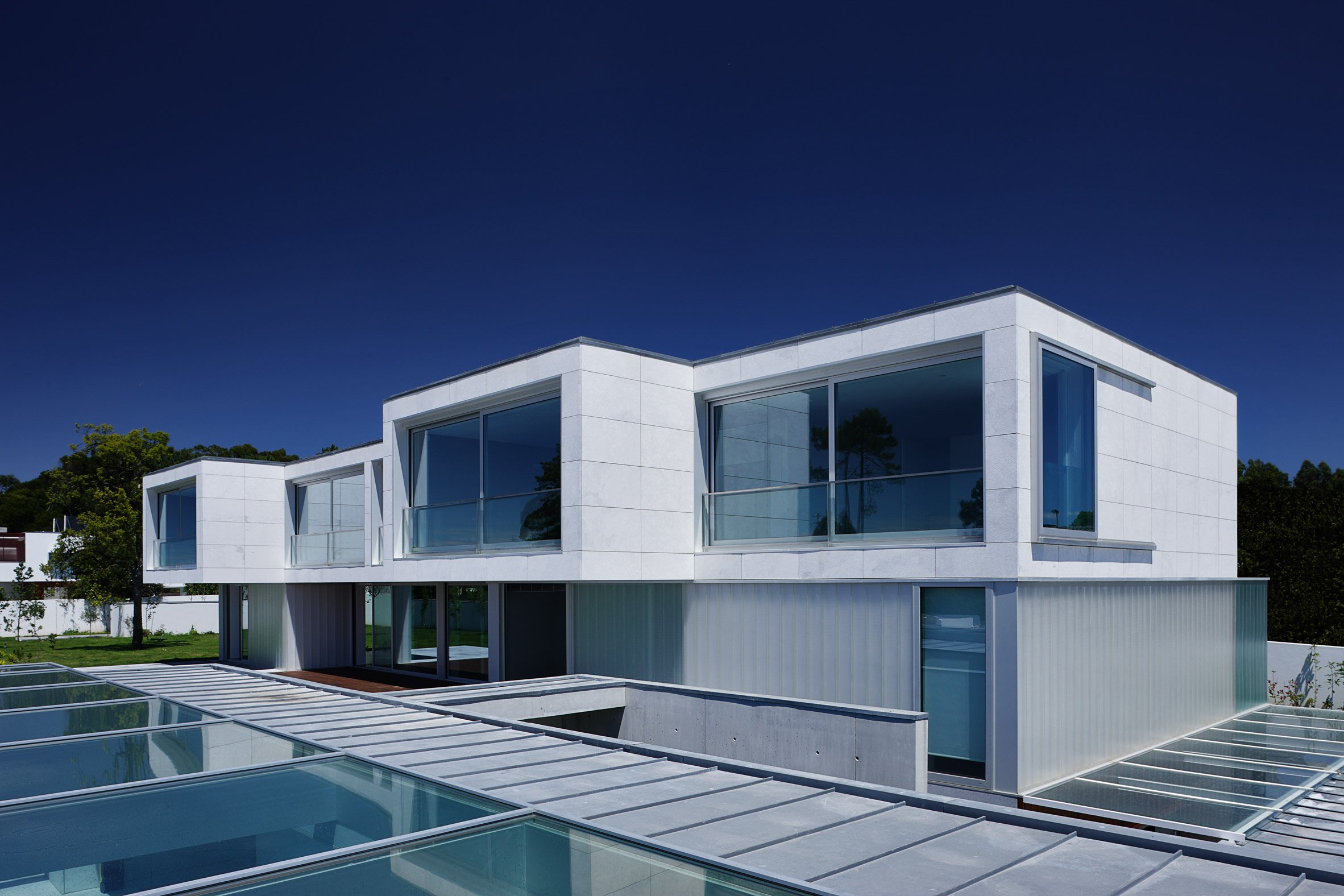 VOA combines wood, marble and glass in layered composition of Portuguese seaside home