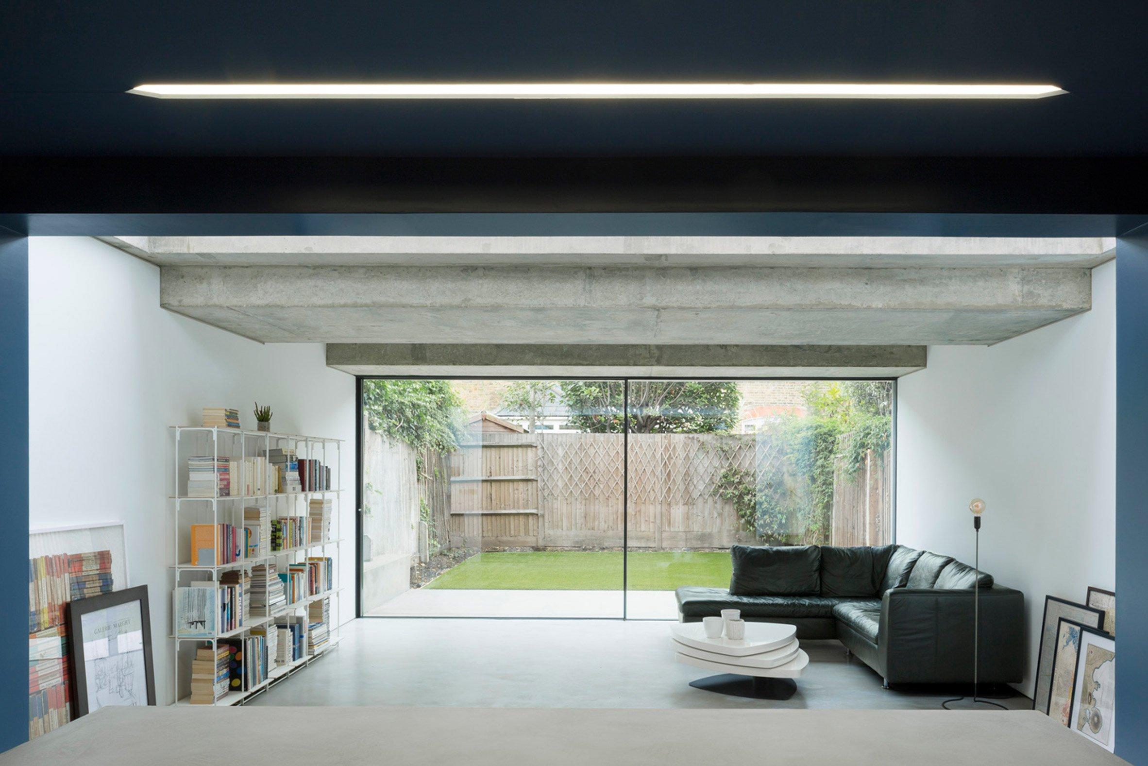London house extension by Bureau de Change Architects features dark blue kitchen and bright white lounge