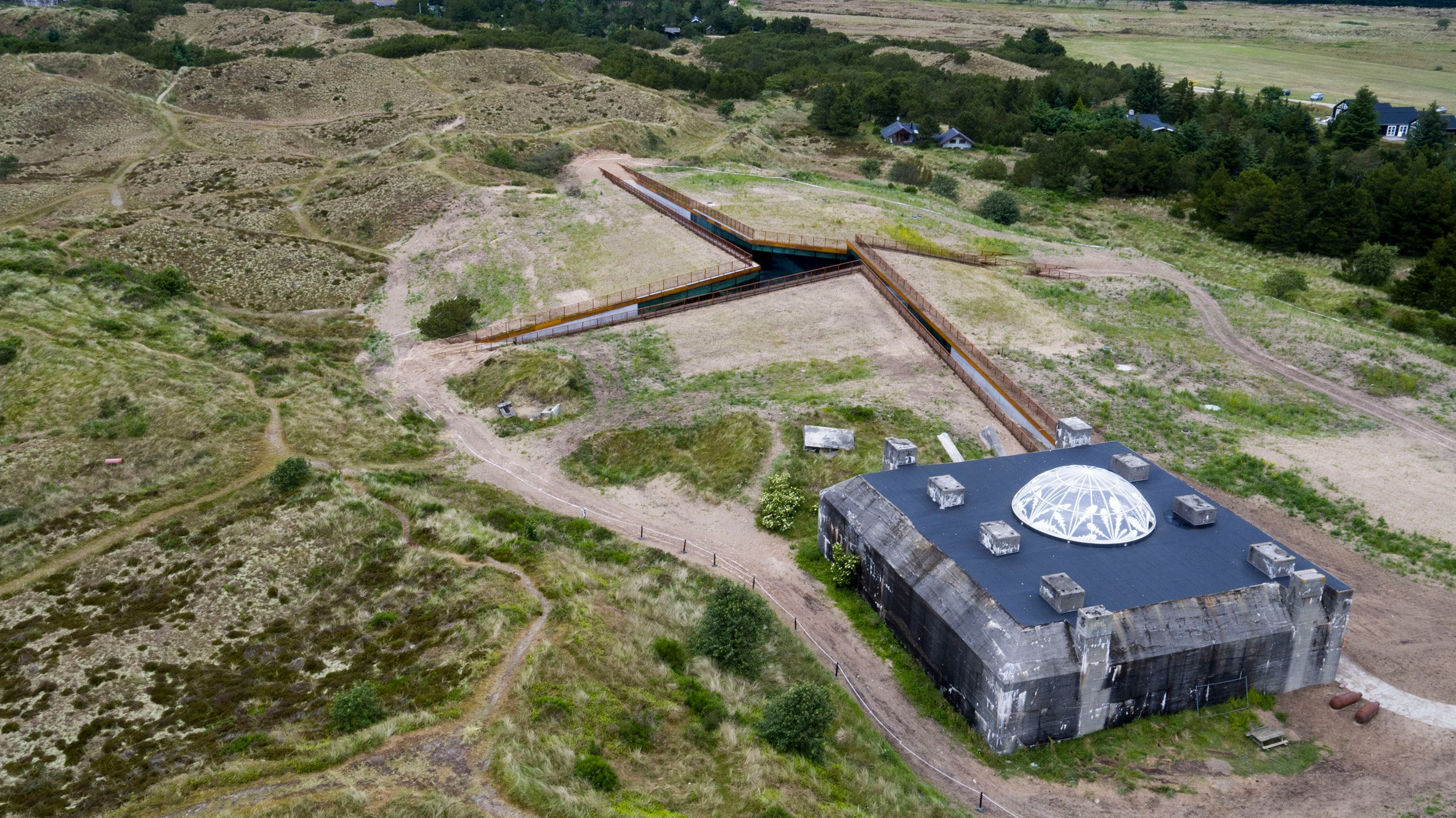 BIG creates subterranean museum by carving channels into dune by Nazi bunker
